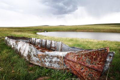 Rusted boat at Johnson Mesa stock pond in New Mexico