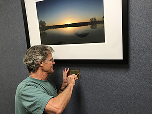 "Tim Keller installing ""Oasis State Park at Sunrise"" at Roosevelt General Hospital, Portales, 2018"